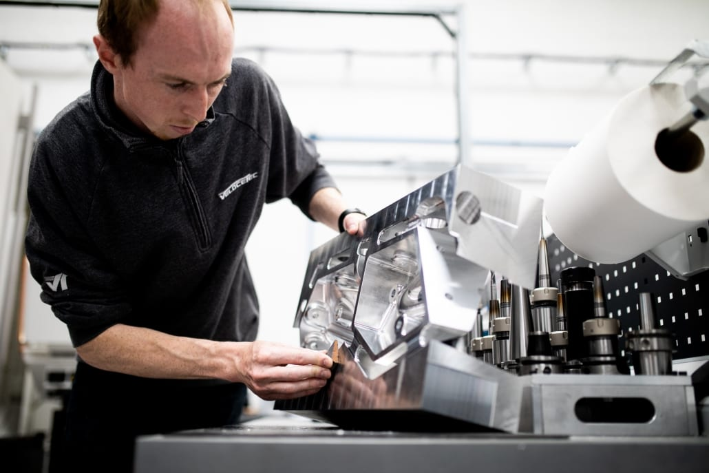 Photo of a Velocetec team member finishing a part