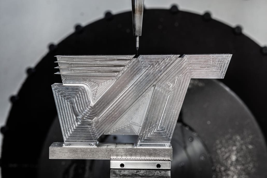 Photo of the Velocetec logo device being machined from solid metal